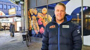 En man i vinterkläder står utanför Citymarket i Borgå. Han ler och tittar mot kameran.
