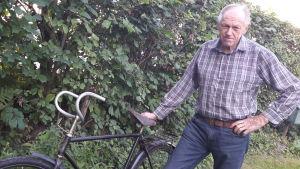Sture Walls står vid en gammal cykel, modell Felix Special.