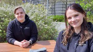 En ung man och en ung kvinna sitter på var sin sida av ett bord, men så att de är vända mot kameran. Den unga kvinnan sitter närmast kameran, medan mannen har sina händer knäppta på bordet. Båda tittar in i kameran med ett litet leende på läpparna.