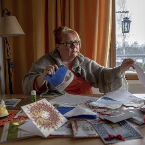 Pitkäaikaistyötön Jaana Saikkonen askartelee joulukortteja kotonaan Pukinmäessä Helsingissä.