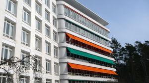 En gammal sjukhusbyggnad med gröna och orange markiser vid fönstren.