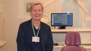 En kvinna, tandläkare sitter bredvid en tandläkarstol. Hon ler.