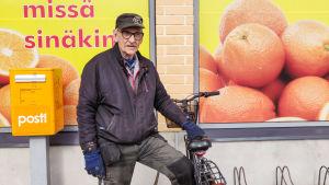 En äldre man håller i en cykel. Han står utanför en mataffär.