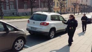Två parkeringskontrollanter tittar på bilar, om parkeringsavgiften är betald.