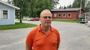 Man med orange skjorta och glasögon. I bakgrunden bl.a. byggnader.