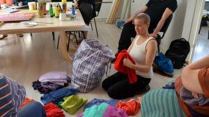 En kvinna sitter på knä och lägger ut högar med kläder framför sig