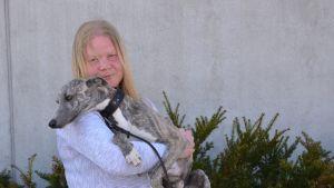 Heidi med sin hund i famnen.