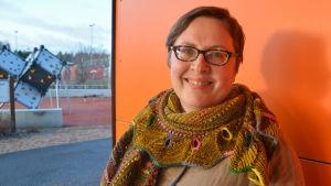 kvinna i grann sjal framför orange vägg