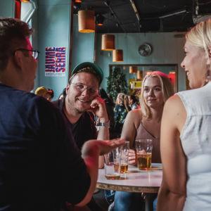 Kaksi naista ja kaksi miestä ravintolapöydän ääressä juovat olutta ja juttelevat.