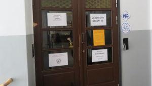 En stängd dörr med många uppsatta appar. Det står bland annat Vänstugan Ekenäs rf, matutdelning, stängt (pga coronaepidemin).