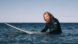 Karaktären Erik sitter på sitt surfbräde ute till havs.