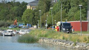 Svart skåpbil och ambulans står på väg intill en småbåtshamn.
