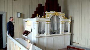 Kantor står brevid gammal orgel.