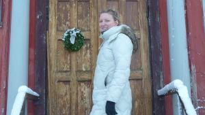 En kvinna står på trappan utanför ett hus med  trädörr med dörrkrans