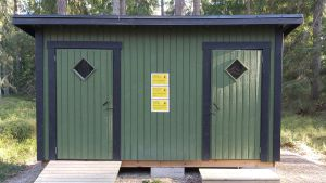 En grön liten byggnad med offentliga toaletter. På fasaden finns gula varningslappar.