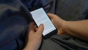 En person ligger i sängen och kollar på sin mobilskärm vad det står.
