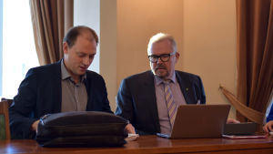 Två män sitter vid ett bord och ser ner mot några papper. Framför den ena mannen finns en bärbar dator och den andra har en portfölj.