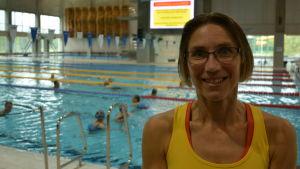 Susanna Vuori, en dam med en gulröd topp och glasögon, står vid en simbassängskant.