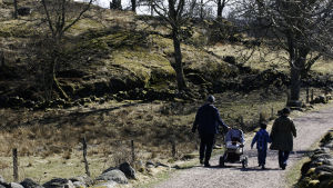 Två vuxna och två barn, ett i barnvagn, ute på promenad i naturen.