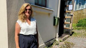 En kvinna står framför en vit husvägg.