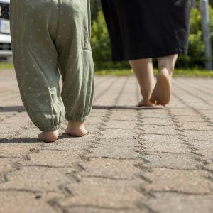 Äidin ja lapsen paljaat jalat pihamaalla
