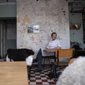 Nick Victorzon sitter vid ett litet bord vid en mastig vägg på sin restaurang.