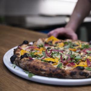Närbild på en färdiggräddad pizza på en tallrik.
