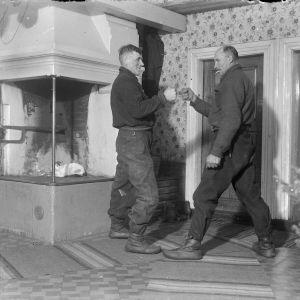 """Två män leker """"knokas"""", där man turvis slår på varandras knutna händer, allt hårdare. Den som tål mest vinner. Bilden är tagen 1937 i Korsnäs, Harrström."""