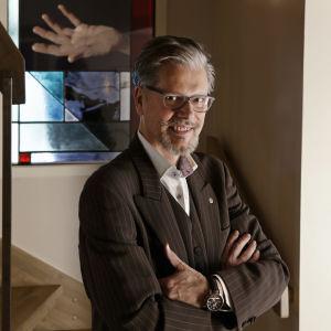Suunnittelija, taiteilija Markku Piri taustallaan lasimaalaus nimeltään Kaipuu.