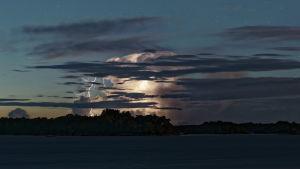 Ett vackert moln som genomskärs av blixtar i skymningen.