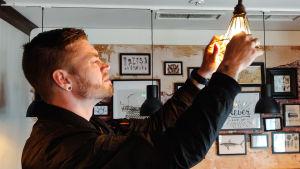 En ung man skruvar på en hängande lampa.