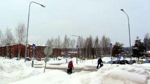 Fotgängare korssar gata i vinterlandskap.