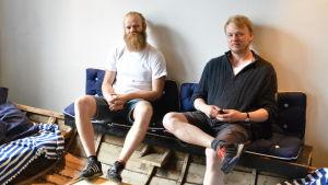 Nyblivna krogägare Salonen och Ölander i en roddbåt ombyggd till soffa