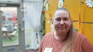 Katri Alifrosti-Holmberg, en dam med långt ljust hår i en hästsvans och en rosa tröja, står vid gula skåp.
