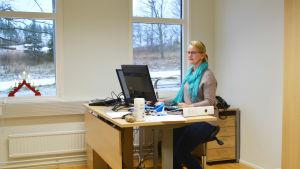 Kvinna sitter bakom skrivbord och jobbar i kontorsrum.