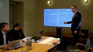Stadsdirektör Jukka-Pekka Ujula talar framför en tv-skärm i ett litet rum i stadshuset i Borgå
