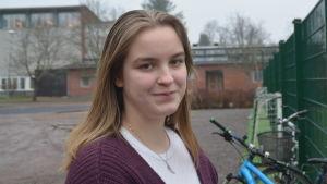 En ung kvinna ute på skolgård. Karis svenska högstadium och Karis-Billnäs gymnasium i bakgrunden.