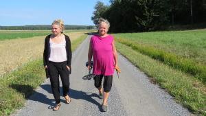 En yngre kvinna, mest klädd i svart och en äldre kvinna klädd i anilinröd t-skjorta och med en metalldetektor i handen går längs en sandväg. Sommar och sol. Åkrar.