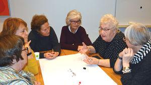 Sex äldre damer sitter kring ett bord och diskuterar. Framför sig har de ett stort vitt papper.
