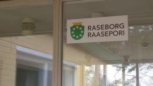 En skylt på en glasdörr med texten raseborg och stadens gröna vapen med krans av vita blommor.