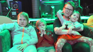Kvinna med tre barn i en soffa.