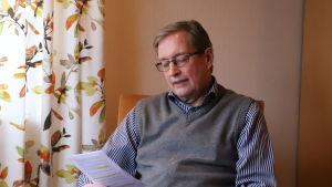 Kjell Wennström sitter i en stol och tittar på ett papper.