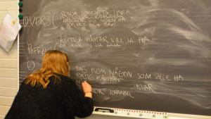 """ord, meningar, verser och refräng skrivs på griffeltavlan. En flicka i svart skjorta står med ryggen mot kameran. Skriver """"riktiga hästar vill vi ha"""""""