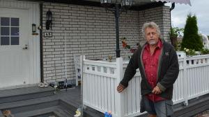 En man som står invid ett tegelhus.