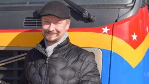 En man i keps som står framför en av Sirkus Finlandias bilar.