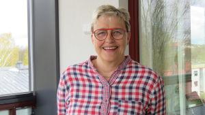 En kvinna med blont kort hår och glasögon och röd-blå-vitrutig skjorta står ute på en inglasad balkong. Hon ler stort.