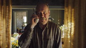 Nisse (Peik Stenberg) står med en telefonlur i handen och lyssnar.
