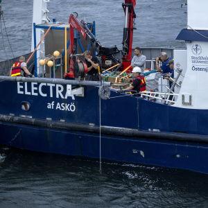 Flygfoto av det blåa forskningsfartyget Electra af Askö taget den 11 juni 2021 under den tredje dagen av den svensk-estniska dykoperationen vid MS Estonias vrak i Finska viken.