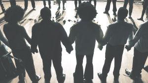 Människor står hand i hand