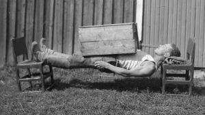 """En man leker """"ligga lik"""", där kroppen ska vara så styv att man ligger mellan två stolar med bara nacken och hälarna som stöd. Bilden är tagen 1932 i Esse."""